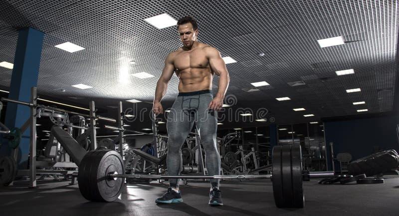 Atleta descamisado muscular atractivo que se prepara para hacer el deadlift i foto de archivo