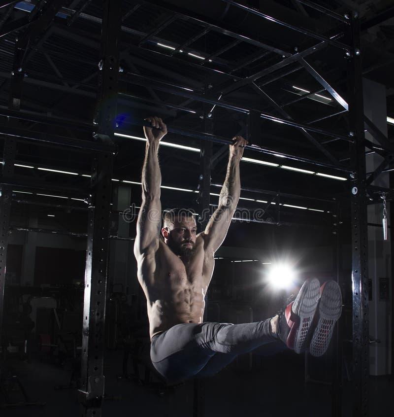 Atleta descamisado muscular que hace ejercicios en barra horizontal adentro fotos de archivo