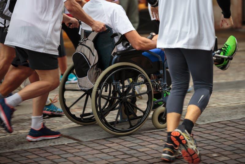 Atleta discapacitado en una silla de ruedas del deporte durante el maratón ayudado por los corredores fotos de archivo libres de regalías