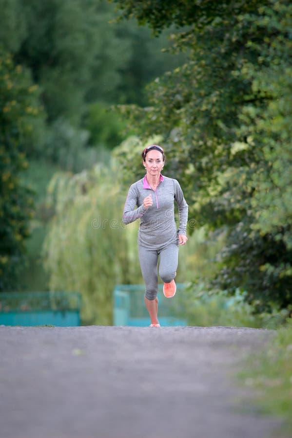 Atleta do corredor que corre na fuga do parque trabalho movimentando-se da aptidão da mulher fotografia de stock