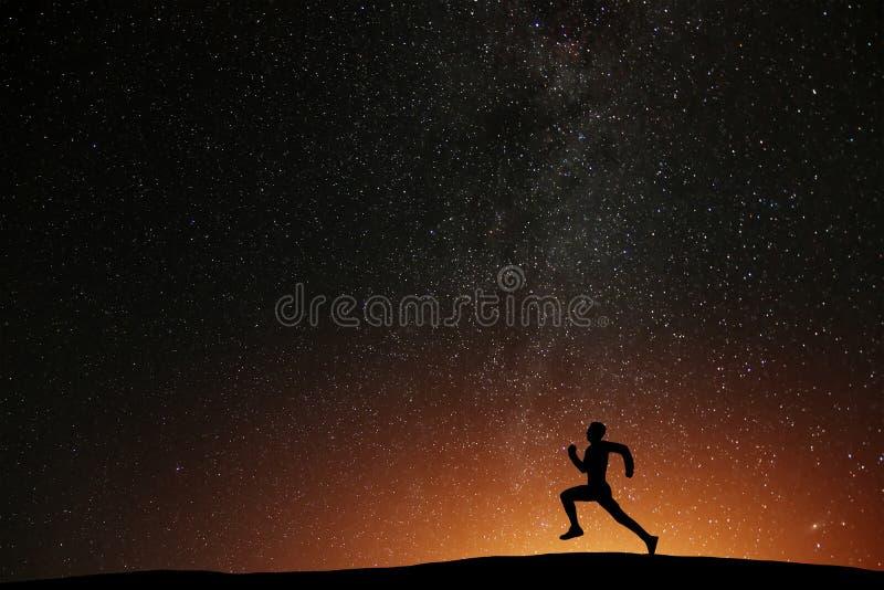 Atleta do corredor que corre no monte com noite estrelado bonita imagens de stock royalty free