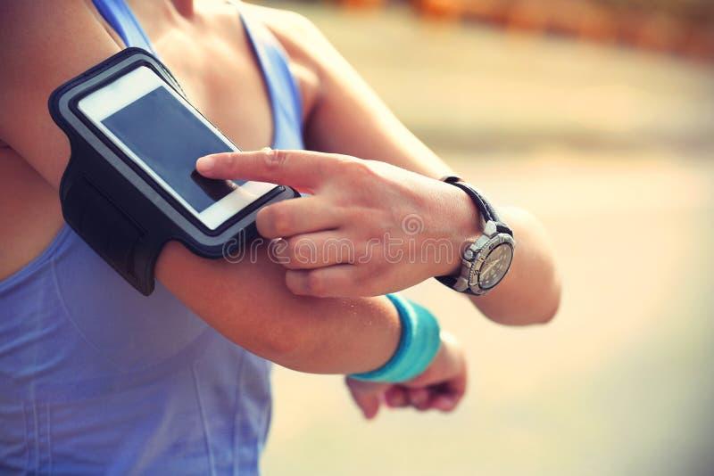 Atleta do corredor que escuta a música da fita esperta do telefone do leitor de mp3 esperto do telefone fotografia de stock