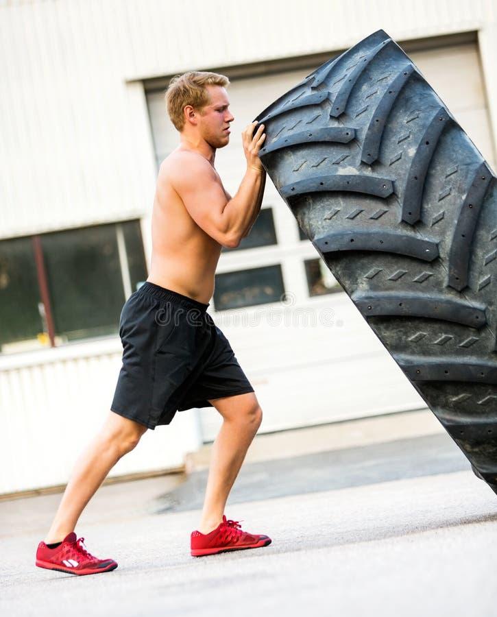 Atleta Doing Tire-Flip Exercise fuera del gimnasio imagen de archivo