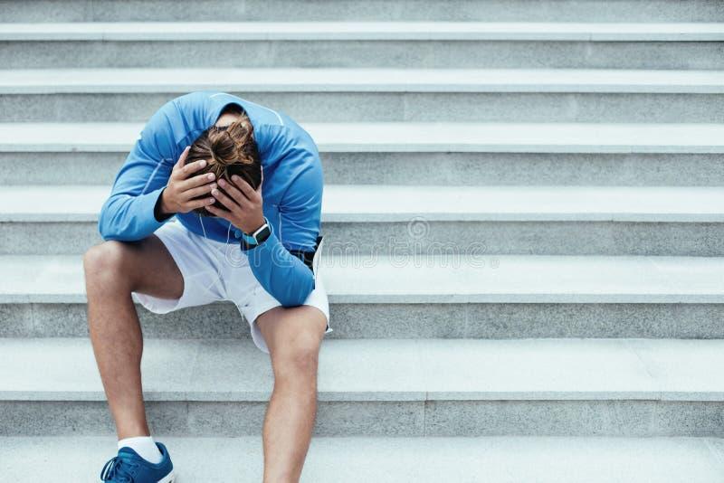 Atleta dopo guasto che si siede sulle scale sulla via e che tiene la sua testa, sul bracciale con il telefono cellulare e sugli s fotografie stock libere da diritti