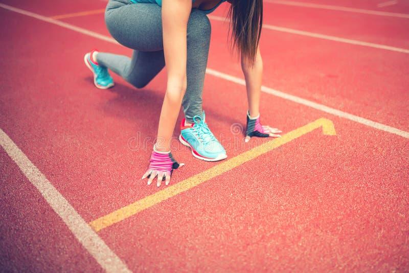 atleta em blocos começar na trilha do estádio que prepara-se para uma sprint Aptidão, estilo de vida saudável fotografia de stock royalty free