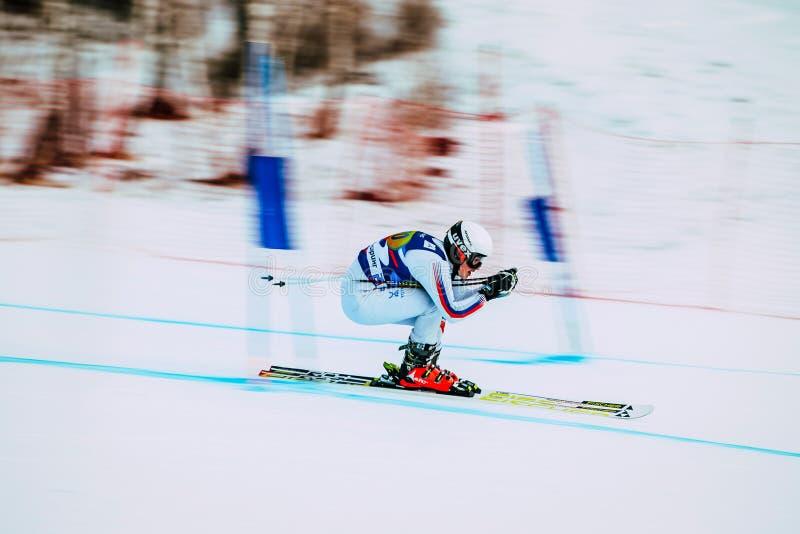Atleta em declive da moça que esquia ao copo do russo da competição no esqui alpino efeito do borrão do fundo imagem de stock