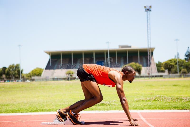 Atleta em um bloco começar aproximadamente a correr fotografia de stock royalty free