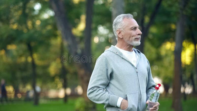 Atleta emeryt pije wodę butelkową po outside szkolenia, sprawność fizyczna obraz royalty free