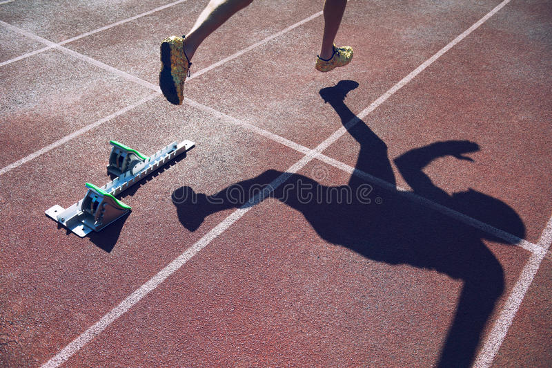 Atleta en zapatos del oro que esprinta a través de línea de salida fotografía de archivo