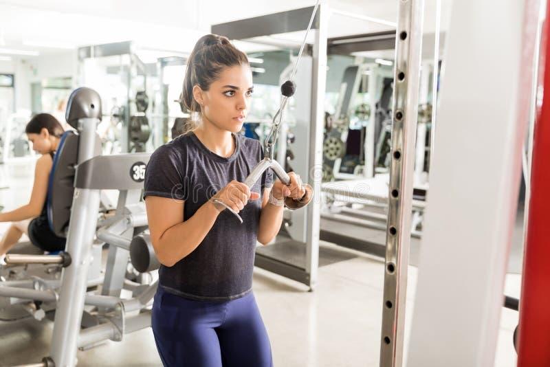 Atleta Exercising Triceps Pushdown alla macchina del cavo della corda immagine stock