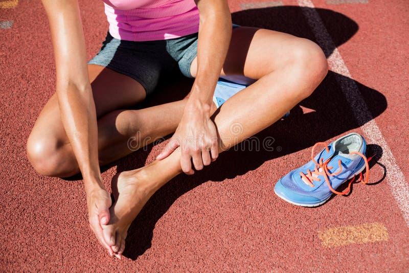 Atleta fêmea com dor do pé na pista de atletismo imagem de stock