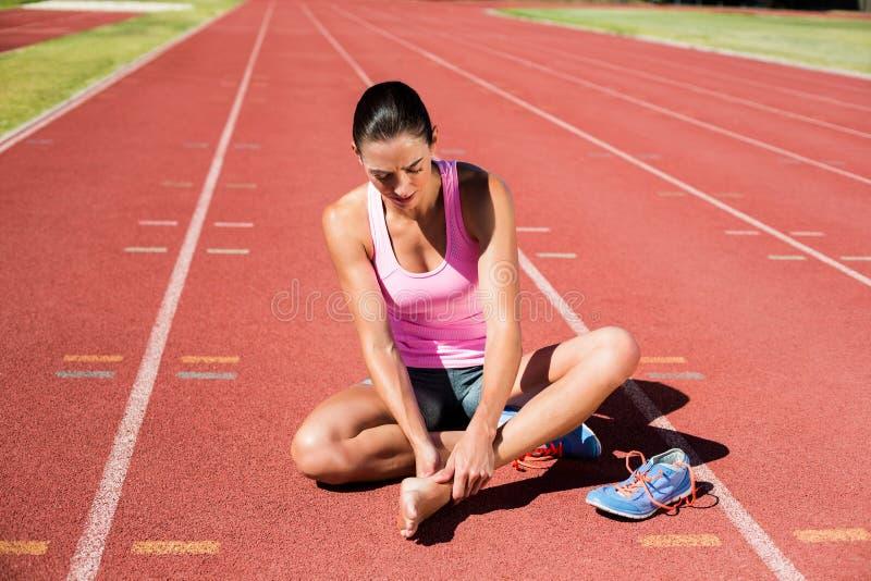 Atleta fêmea com dor do pé na pista de atletismo imagens de stock