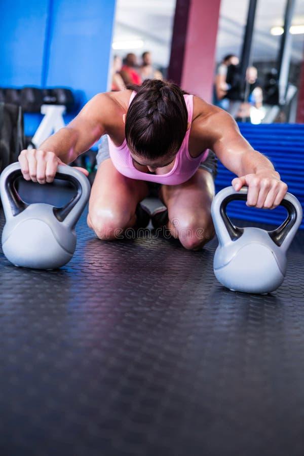 Atleta fêmea com kettlebells no gym fotografia de stock