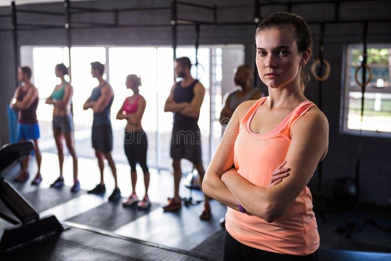 Atleta fêmea com os braços cruzados no gym fotos de stock