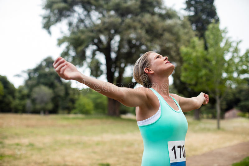 Atleta fêmea com os braços estendido no parque fotos de stock