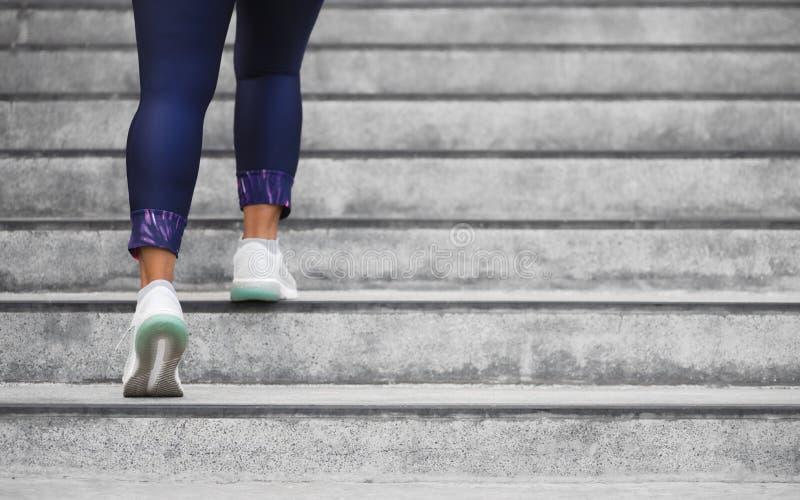 Atleta fêmea do corredor que faz uma escalada das escadas Mulher de corrida que faz a corrida acima das etapas na escadaria na ci fotografia de stock royalty free