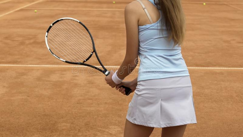 Atleta fêmea magro que salta e que prepara-se para bater a bola de tênis na corte, close up foto de stock