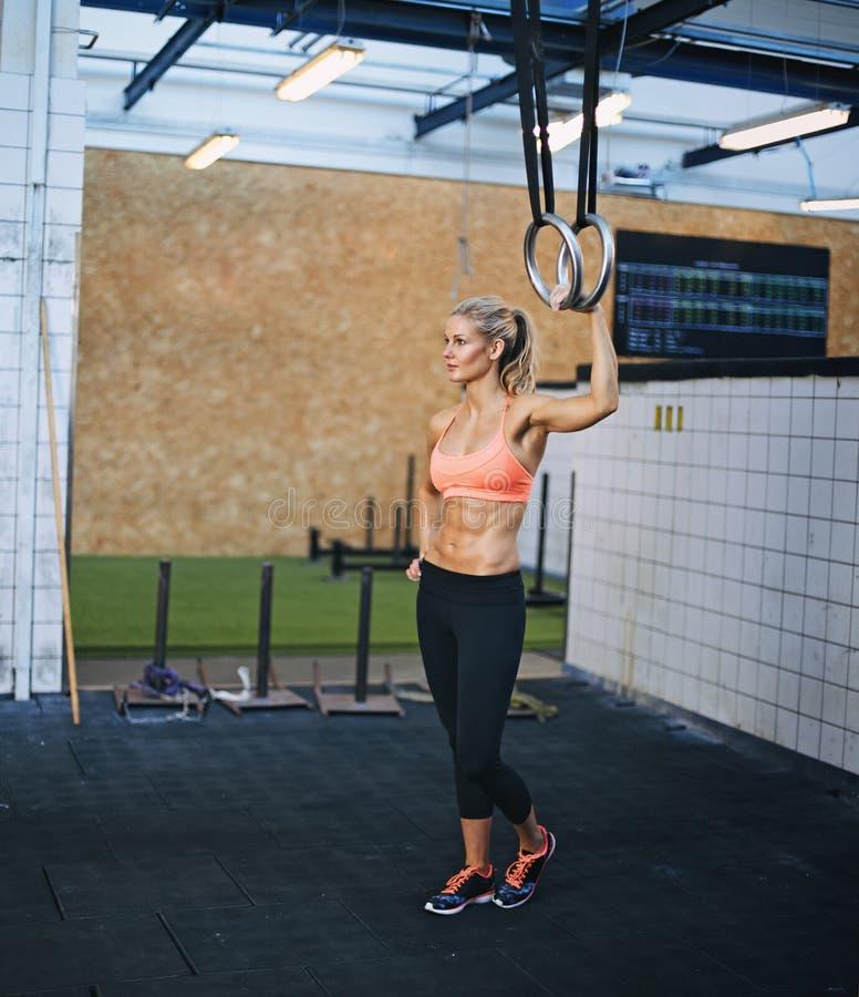 Atleta fêmea muscular que guarda anéis da ginasta imagens de stock