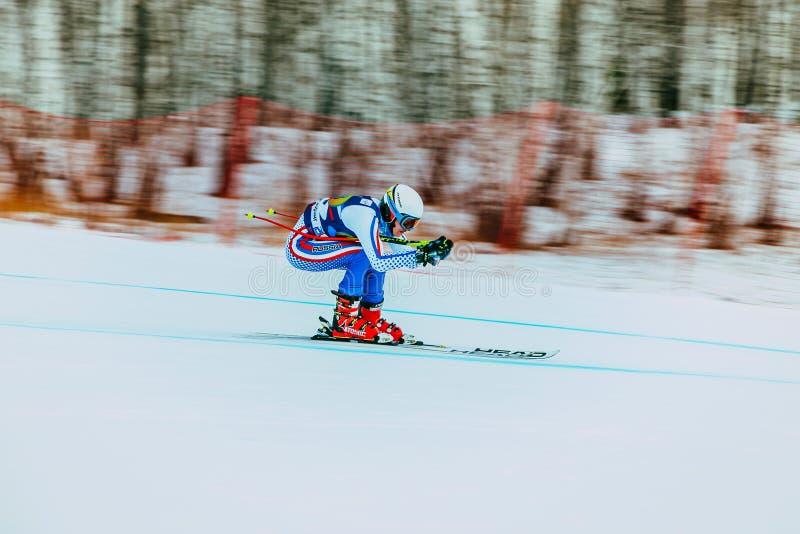 Atleta fêmea novo na competição efeito do borrão do fundo durante o copo do russo no esqui alpino foto de stock royalty free