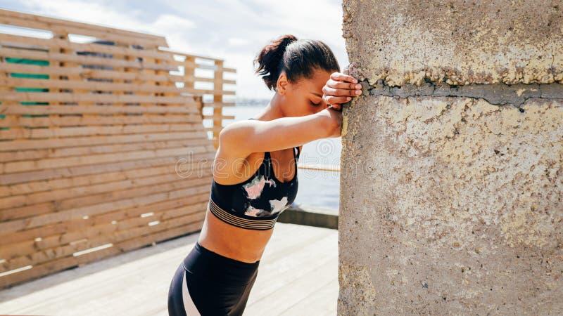 Atleta fêmea novo que toma a respiração profunda durante um exercício imagens de stock royalty free