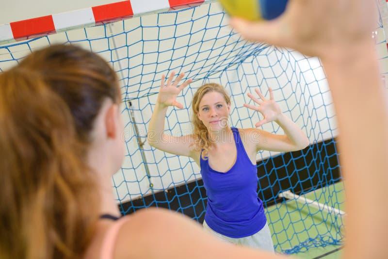 Atleta fêmea pronto para disparar no objetivo do handball foto de stock