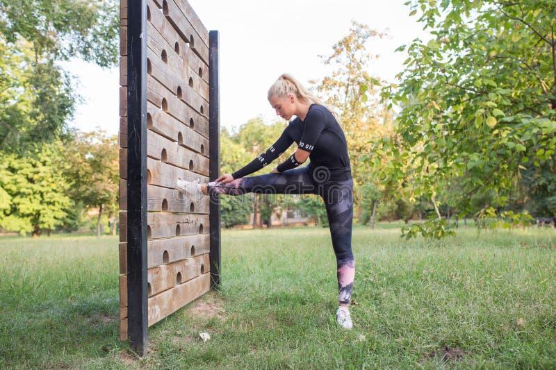 Atleta fêmea que estica seu pé durante o exercício fotografia de stock royalty free