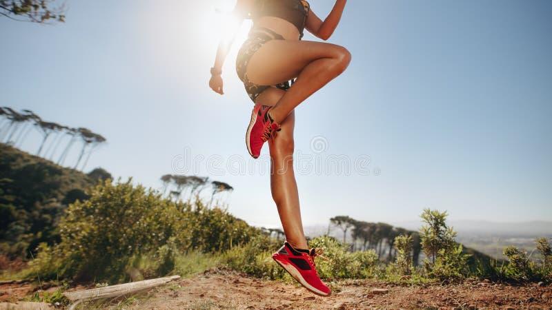Atleta fêmea que faz o exercício em um monte com o sol no fundo Tiro colhido de uma mulher no desgaste da aptidão que aquece a po foto de stock royalty free