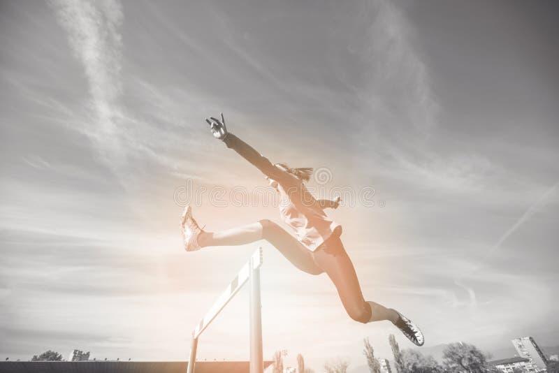 Atleta fêmea que salta acima do obstáculo durante a raça foto de stock royalty free