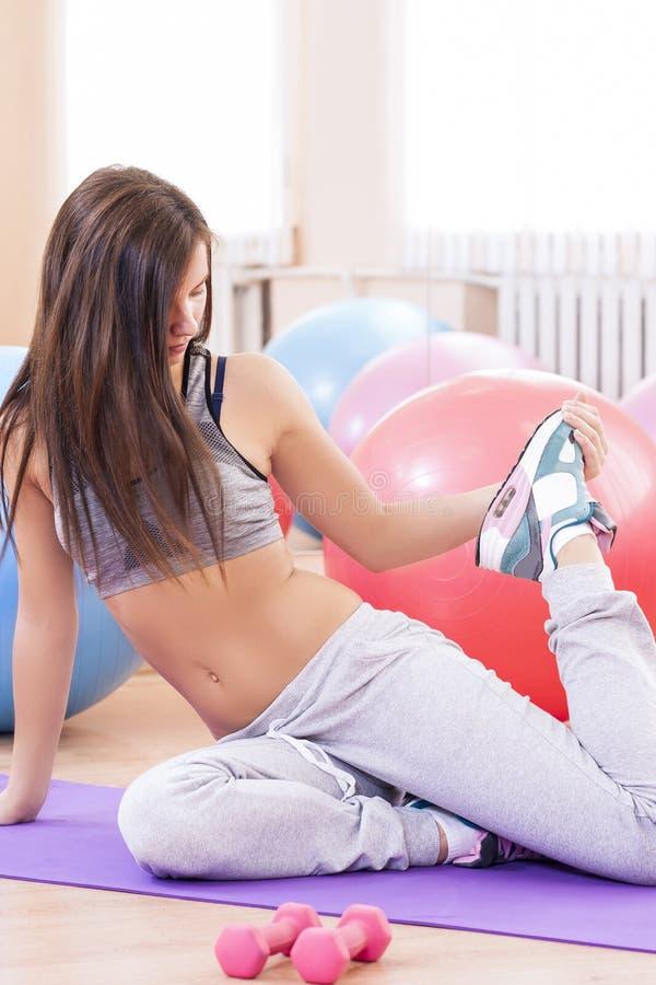 Atleta fêmea 'sexy' caucasiano In Good Fit que levanta com Barbell e que faz o pé que estica exercícios foto de stock royalty free