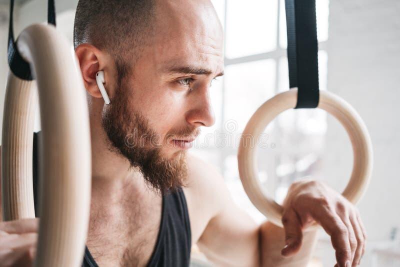 Atleta farpado forte com o fones de ouvido sem fio que guarda anéis crosstraining no salão do crossfit fotografia de stock