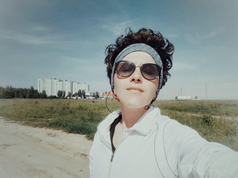Atleta feliz da menina durante um ar livre do movimento com fones de ouvido e nos óculos de sol imagem de stock