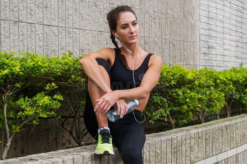 Atleta femminile abbastanza giovane che recupera dopo l'esercitazione o corsoe, sedendosi, ascoltando la musica in cuffie e nello immagine stock libera da diritti
