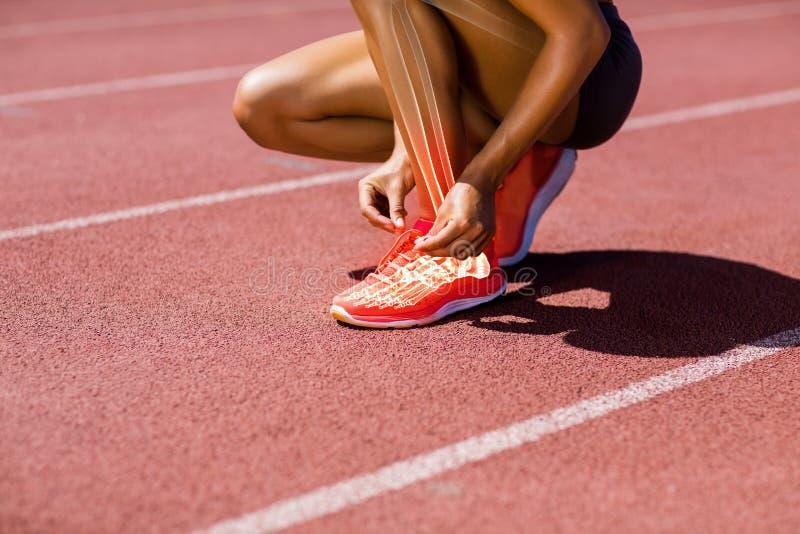 Atleta femminile che lega laccetto sulla pista fotografie stock