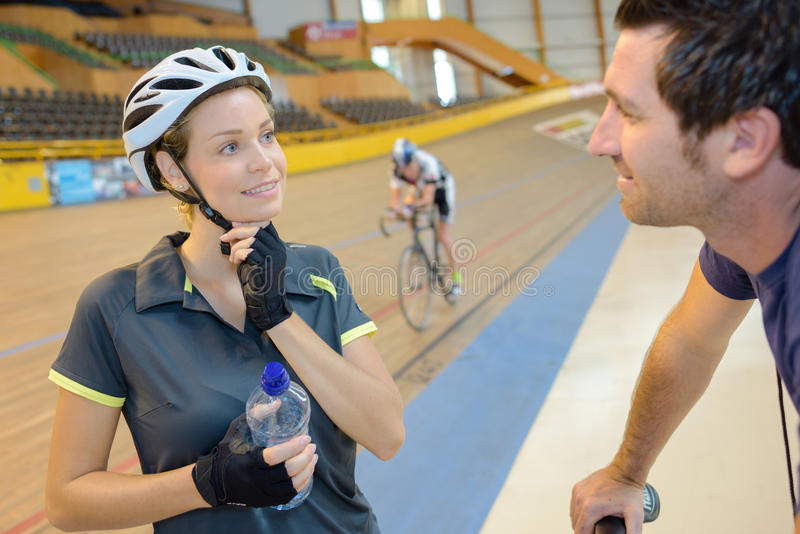 Atleta femminile che parla con la vettura sulla pista del velodromo fotografia stock