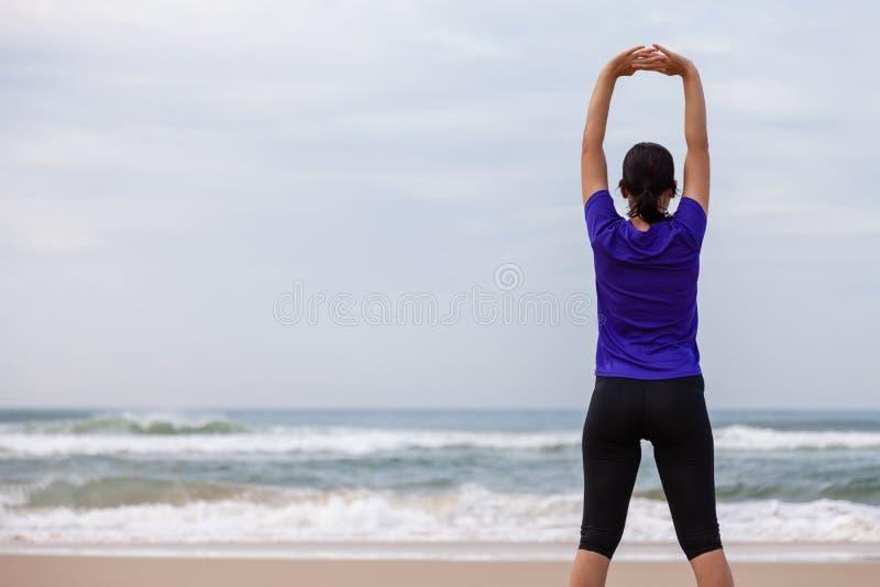 Atleta femminile che si scalda e che allunga il corpo superiore immagine stock