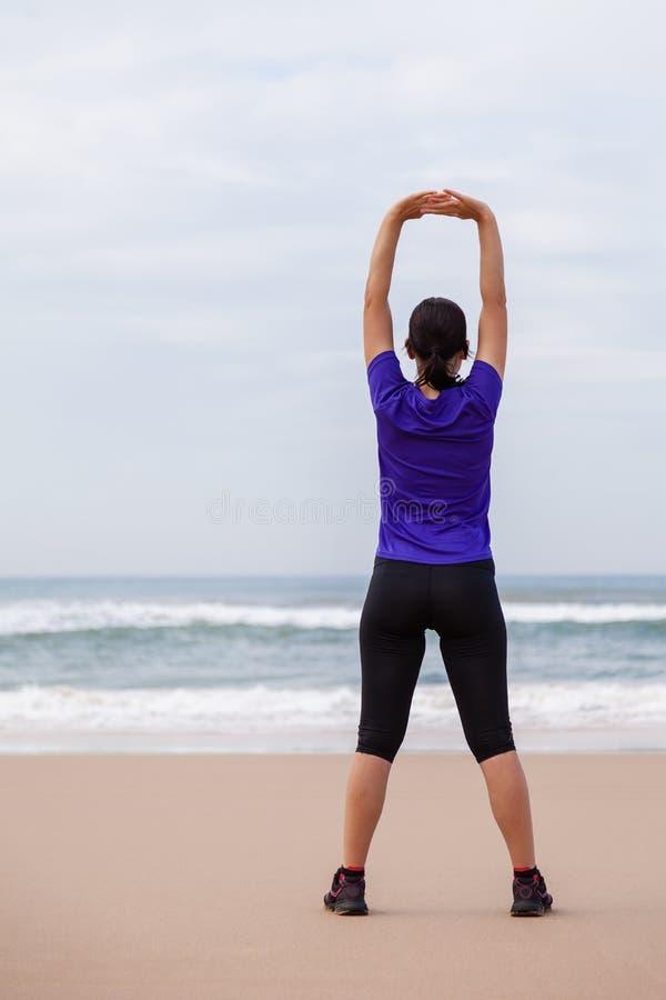 Atleta femminile che si scalda e che allunga il corpo superiore prima dell'correre fotografia stock