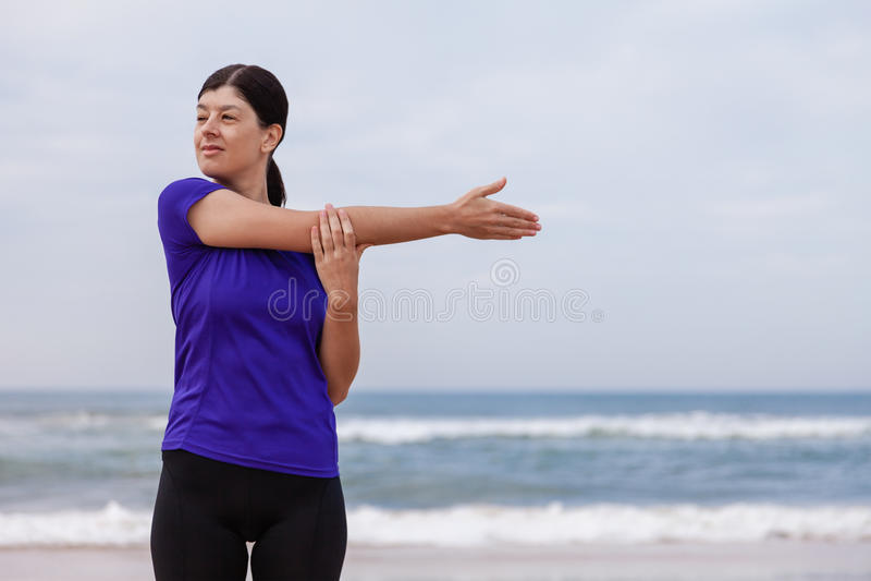 Atleta femminile che si scalda e che allunga il corpo superiore prima dell'correre alla spiaggia fotografia stock
