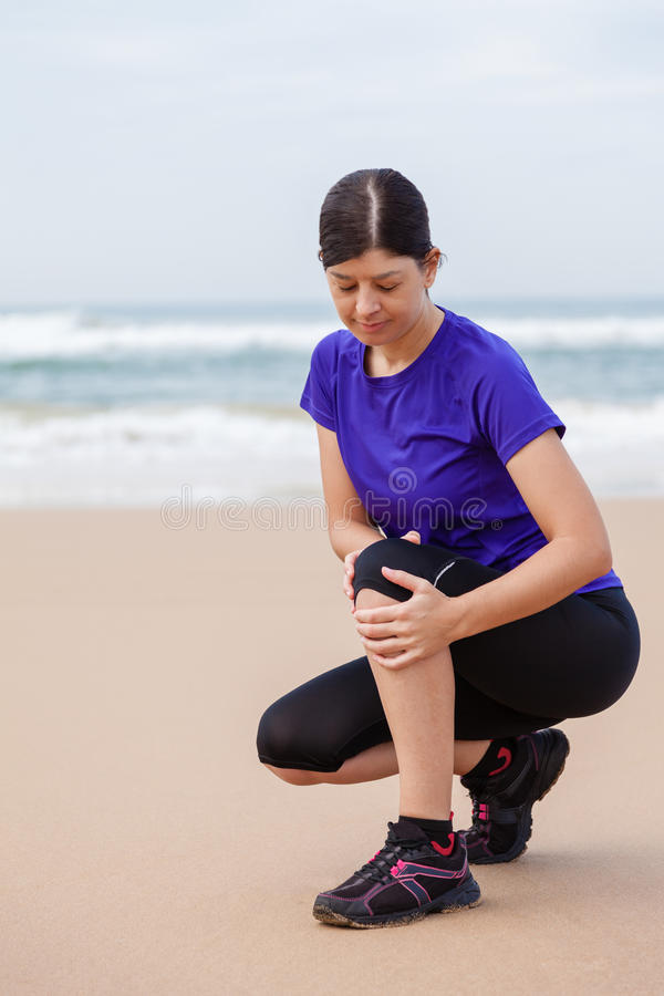 Atleta femminile che soffre da una ferita al ginocchio immagine stock
