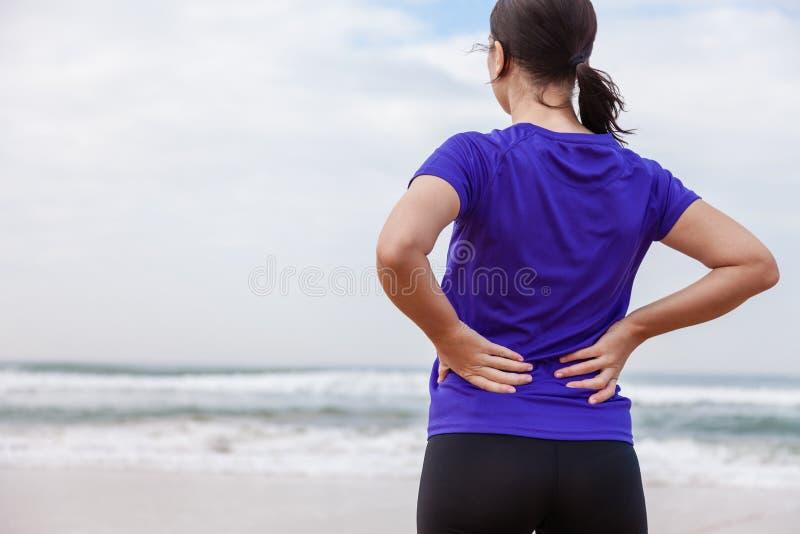 Atleta femminile che soffre da una lesione alla schiena fotografia stock