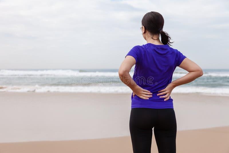 Atleta femminile che soffre da una lesione alla schiena alla spiaggia fotografia stock