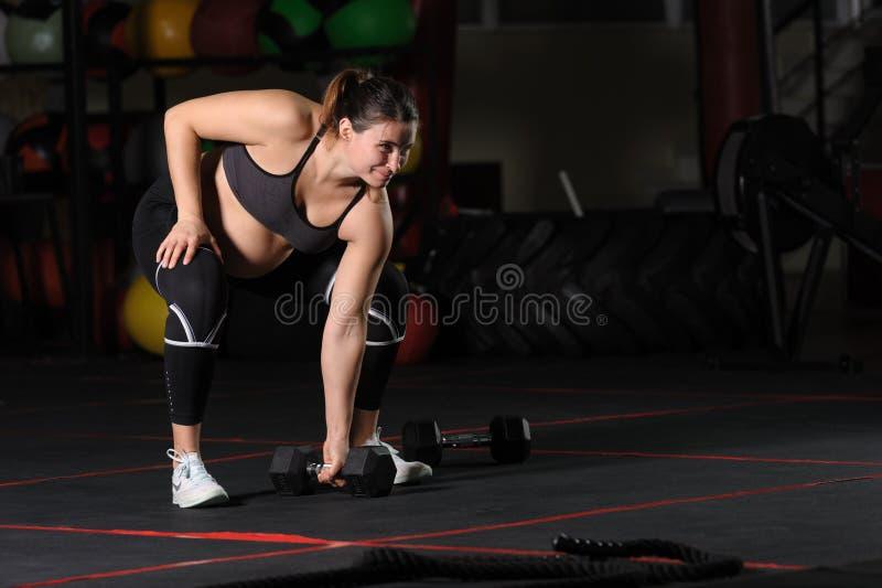 Atleta femminile incinto che fa il singolo deadlift di sumo della testa di legno del braccio fotografia stock
