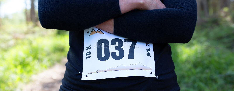 Atleta femminile irriconoscibile della traccia che posa con il numero della corsa immagini stock
