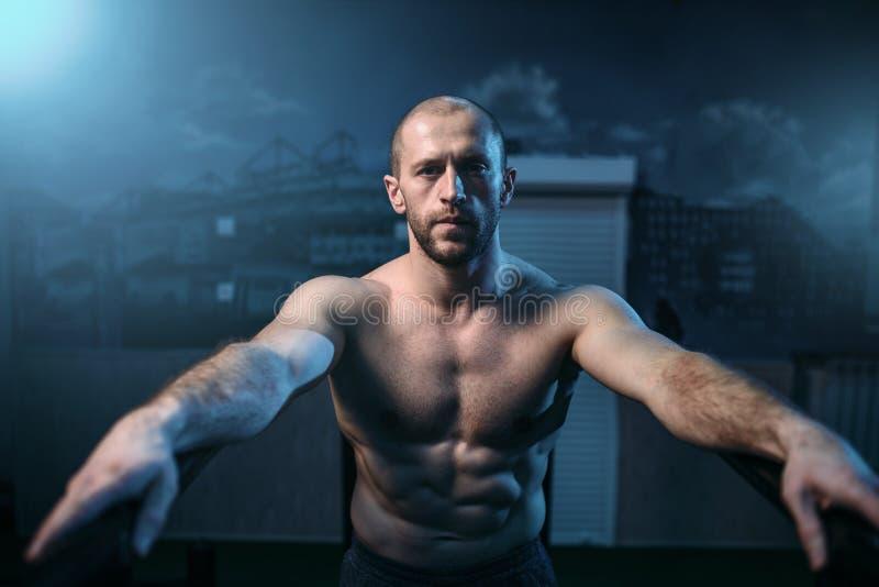 Atleta forte em barras ginásticas no gym imagens de stock