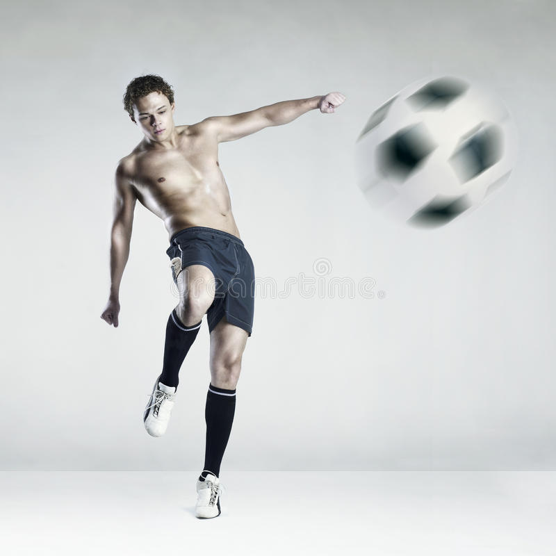 Atleta fuerte que golpea la bola con el pie fotos de archivo