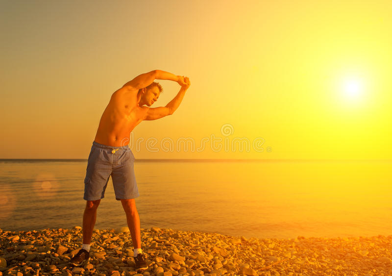 Atleta, giocando gli sport e yoga sulla spiaggia fotografie stock libere da diritti