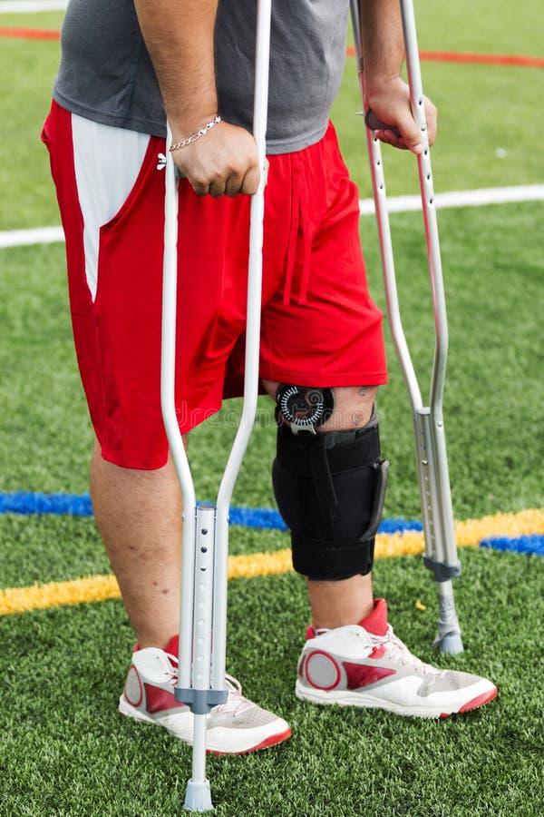 Atleta herido en un apoyo de rodilla en las muletas foto de archivo libre de regalías