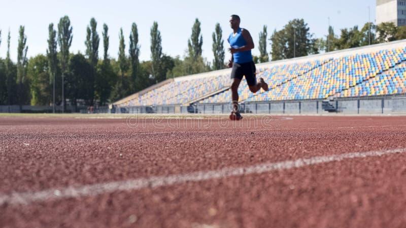 Atleta hispánico útil que corre en el estadio, preparándose para el maratón, deporte fotografía de archivo