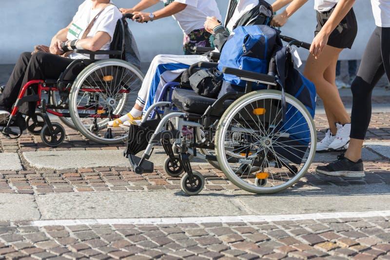 Atleta inhabilitado en una silla de ruedas del deporte durante el maratón ayudado por los corredores femeninos imagen de archivo libre de regalías