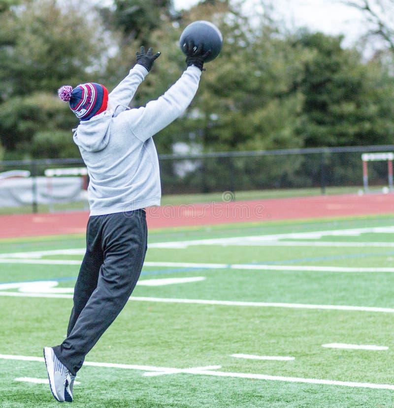 Atleta jogado uma bola de medicina e deixar seus pés fotos de stock royalty free