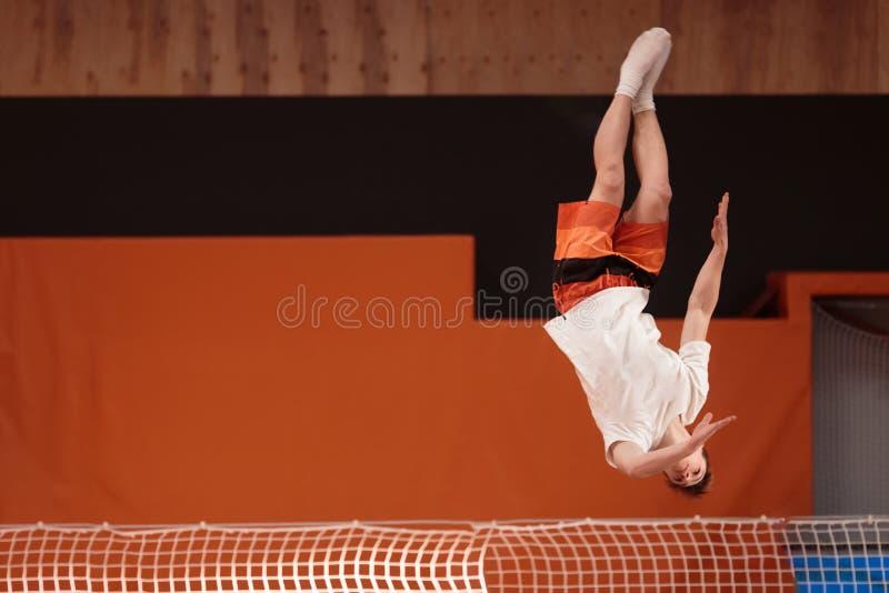 Atleta joven en el trampolín en vuelo agraciado fotos de archivo libres de regalías